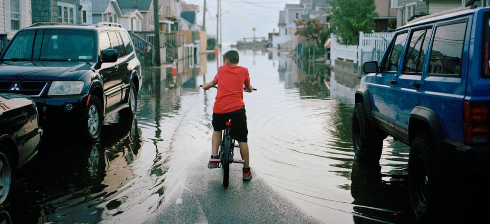 gw-sea-level-rise-boy-on-bike-looking-at-tidally-flooded-neighborhood