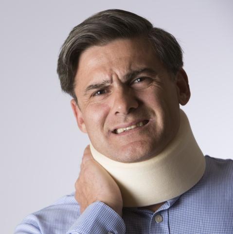 Studio Shot Of Masn In pain Wearing Neck Brace